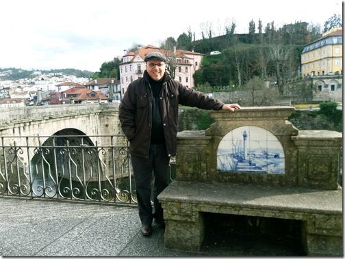 Gilson Santos junto à Ponte de São Gonçalo, em Amarante. No painel de azulejo do banco, o pelourinho e a ponte de Aboadela de Ovelha do Marão.